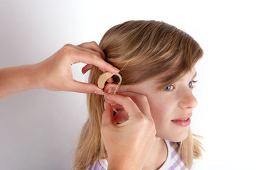Doctor fitting a young girl patient with hearing aid