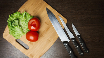 tomato and a kitchen knife on a cutting board