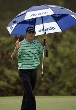 Jonathan Byrd of Sea Island waves to the gallery after finishing the second round in the rain at the Mercedes- Benz Championship golf tournament in Kapalua, Hawaii.