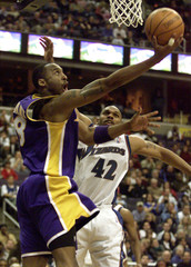 LAKERS KOBE BRYANT ATTEMPTS REVERSE LAYUP AGAINST WIZARDS DURING NBA GAME.