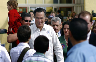Republican presidential candidate Romney greets supporters as he walks to a news conference following a campaign rally in Sweetwater