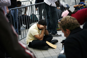 A man sits on the ground while waiting in line to file an application for one of 35 firefighter jobs in Miami
