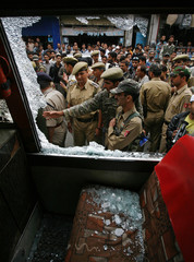 Indian police personnel examine the damage to a passenger minibus after a blast in Srinagar