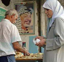 """A Palestinian woman buys """"Catayef"""" Ramadan sweets beneath a picture of ailing Palestinian President ..."""