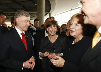 German President Koehler and  his wife Eva Luise listen to Chancellor Merkel after being reelected to office at the Reichstag in Berlin