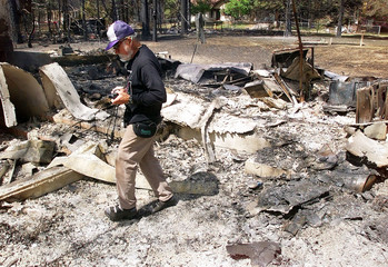 FIRE VICTIM WALKS THROUGH THE REMAINS OF HOUSE.