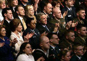 US President George W Bush and first lady Laura Bush sits among members of the armed forces.