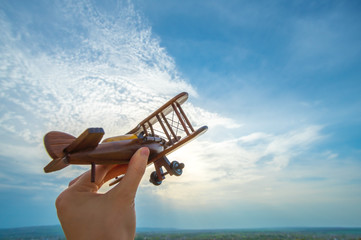 The hand with a wooden plane on the blue sky background