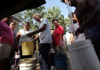 CUBANS FILLING THEIR BUCKETS WITH WATER DELIVERED BY A TANKER TRUCK.