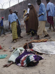 Mogadishu residents stand beside the body of the victim of a roadside explosion in Mogadishu