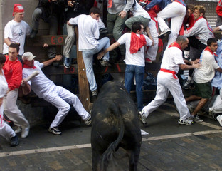 RUNNERS FLEE FROM A FIGHTING BULL DURING THE FIRST RUN OF THE SANFERMIN FESTIVAL.