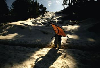Kashmiri earthquake survivor makes his way through snow covered mountain in Pakistan
