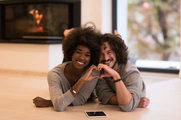 multiethnic couple showing a heart with their hands on the floor