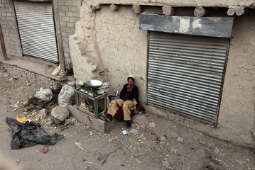 An Afghan street seller watches a U.S. MRAP vehicle transport U.S. Army soldiers near Shembawut village in Khowst province