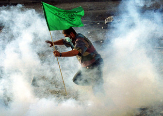 PALESTINIAN PROTESTER IS ENGULFED IN A CLOUD OF TEAR GAS DURING CLASHES IN RAMALLAH.