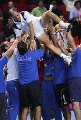 Italy's coach Barazzutti is held up by team members while they celebrate their victory over Belgium in final of Federation Cup tennis tournament in Charleroi