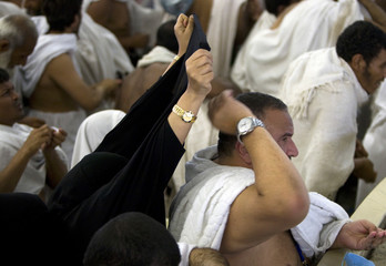 A woman protects the back of her husband's head from stones with her scarf as Muslim pilgrims throw stones at pillars symbolising the devil in Mina
