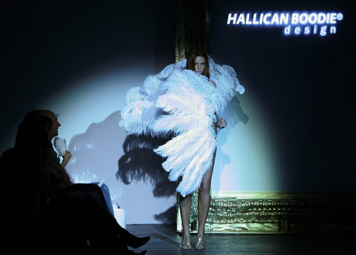 Model covers herself with feathers as she wears design by Hallican Boodie during swimwear collection show at Australian Fashion Week in Sydney