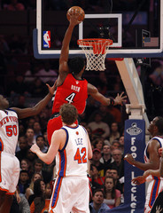 Chris Bosh of Toronto goes in for a slam dunk past Zach Randolph (L) and David Lee of New York during the first half of the NBA basketball game between the New York Knicks and the Toronto Raptors, in New York