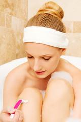 Young caucasian woman shaving legs