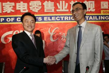 Gome CEO Huang and China Paradise chairman Chen Xiao shake hands during a news conference in Beijing