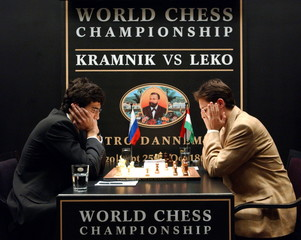 Title holder Vladimir Kramnik (L) of Russia and challenger Peter Leko (R) of Hungary study the board..