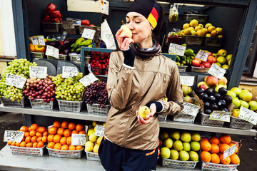 A girl holding and smelling vegetables at a grocery market