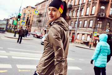 A girl runner walking after run across a crossroad of Saint Peterburg