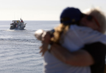 Couple on shore embrace as a boat of activists leaves the Cyprus port of Larnaca for Gaza, in defiance of an Israeli navy blockade