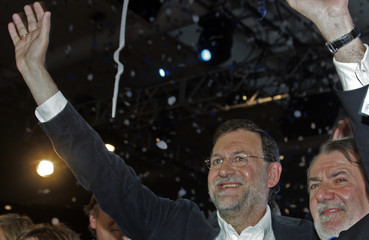 Spain's opposition Popular Party leader Mariano Rajoy and Spain's Jaime Mayor Oreja wave during the final European Parliament election rally in Madrid