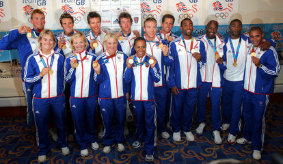 British Olympic gold medalists pose with their medals after their arrival at Gatwick airport.