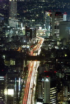 A stream of lights flow down a busy Toyko street in a time exposure photograph August 25, 2003...