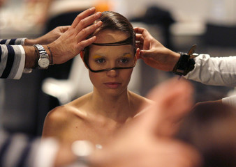 Model is reflected in a mirror as she has make-up applied before Colombian designer Olga Piedrahita's show during Latin America fashion show in Madrid