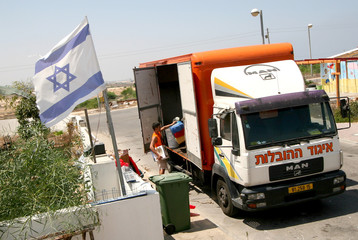 Worker from moving company loads truck at Elei Sinai settlement in northern Gaza Strip.