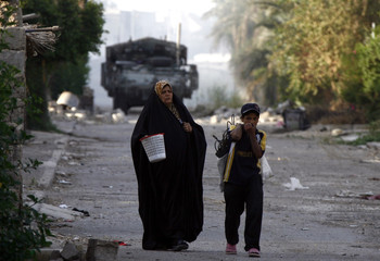 A woman and a boy walk on a street as U.S. soldiers with 2nd Platoon, G Company, 3rd Squadron 2nd Stryker Cavalry Regiment (not pictured) patrol the area, in Baghdad
