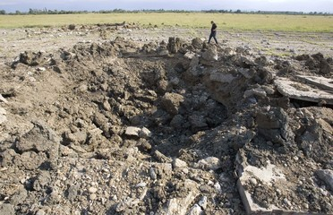 A man walks near a crater which the Georgian military say was created by a Russian bomb dropped at Kutaisi airport