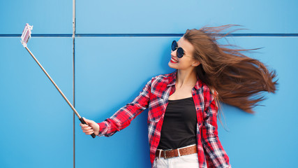 Fashion portrait of pretty smiling and woman in sunglasses with smartphone against the colorful blue wall. Make selfie. Flying hairs