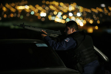 A federal police agent takes up position during an operation in the suburb of Santa Catarina in Monterrey