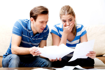 Worried couple after calculating bills sitting at home