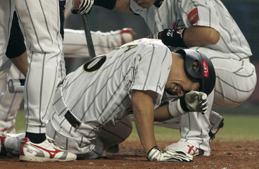 Japan's batter Hirokazu Ibata reacts after being hit by a pitch from the Philippines' pitcher Darwin Dela Calzada during the sixth inning of their 24th Asian Baseball Championships game in Taichung