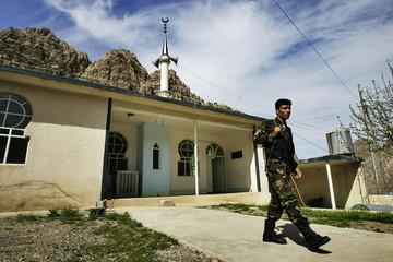 A Kurdish peshmerga soldier walks away from a mosque in the village of Sekanian Sheik Bakh, where Ku..