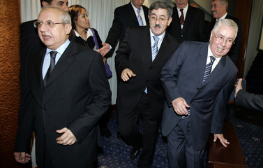 Algerian PM Ahmed Ouyahia smiles as he walks with President of Algerian Parliament Abdelaziz Ziari and President of the Upper House Abdelkader Bensallah in Algiers