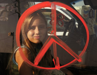 Jaycee Kane is framed by a peace symbol painted on her van as she takes a break from traffic in east Houston
