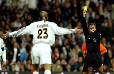 Real Madrid's English player David Beckham (L) receives a yellow card from referee Luis Medina durin..