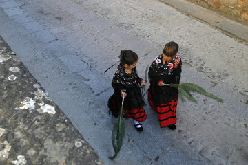 "Young girls dressed as ""pinorras"" carry pine branches as they wait for the start of a procession during the Pinochada festival in Vinuesa"