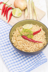 Instant noodles in bowl on wood background