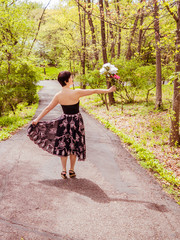 An Asian lady is holding a bunch of flowers and walking in forest