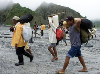 Filipino aetas tribesmen carrying shovels and food supplies trek 15 kilometers to reach the crater o..