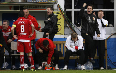 Standard Liege's trainers and staff celebrate after scoring against Ghent during the last match of the Belgian soccer league in Ghent