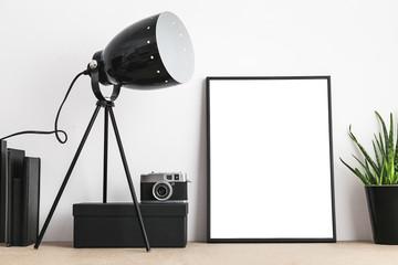 Black empty frame, stylish lamp, camera, books on home or studio.